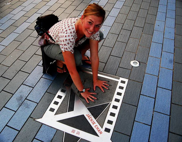Amie with Jackie Chan's handprints and star on Avenue of the Stars in Kowloon.