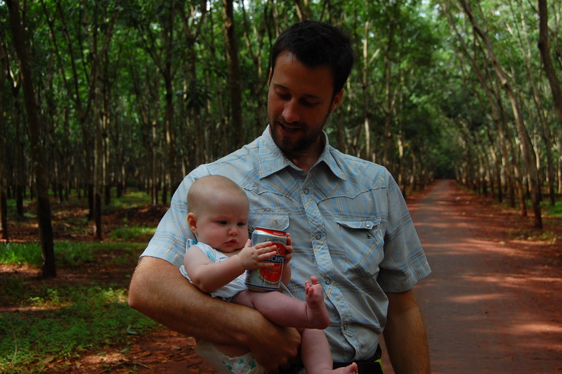 Aya holding dad's beer in the rubber plantation